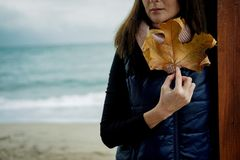 Young Woman with Gold Autumn leaf against the sea in rainy day Royalty Free Stock Images