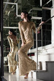 Young woman in gold dress on stairs Stock Photos