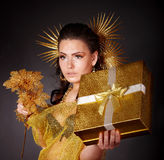 Young woman with gold feather on grey background. Royalty Free Stock Photo