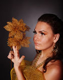 Young woman with gold flower on grey background. Stock Photography