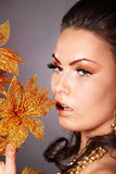Young woman with gold flower on grey background. Royalty Free Stock Images