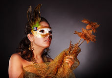 Young woman with gold mask and flower. Royalty Free Stock Image
