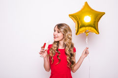young woman with gold star shaped balloon smiling and drinking champagne over white background Royalty Free Stock Photos