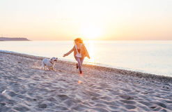 Young woman with  golden retriever on the beach Stock Photography