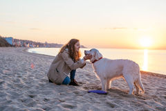 Young woman with  golden retriever on the beach Royalty Free Stock Photography