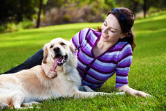 Young woman and golden retriever in the grass stock image