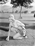 Young woman on a golf course placing a golf ball Stock Photography