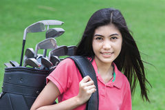 Young woman on a golf course. On a sunny autumn day in the green background Stock Photo