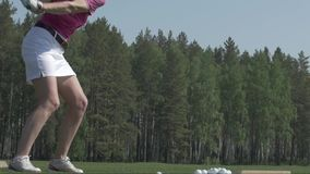 Young woman golf player training on green with club. Girl kick the ball stock video
