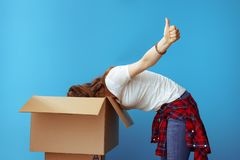 Young woman got into box and showing thumbs up on blue royalty free stock images