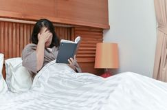 Young woman got headache read a book on bed. Young Asian woman got headache read a book on bed, Health care concept Stock Photography