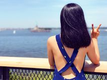 A young woman on Governors Island. A asian young woman back figure facing Statue of Liberty on Governors Island in New York United states Royalty Free Stock Photo