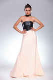 Young woman in gown standing with hands on hips Royalty Free Stock Images