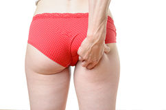 Young woman grabbing excess fat on her buttocks Stock Images