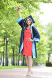 Young woman graduate. Caucasian young woman graduate wearing cap and gown holding diploma stock photo