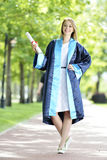 Young woman graduate. Caucasian young woman graduate wearing cap and gown holding diploma royalty free stock photography