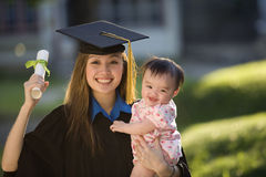 Young woman graduate holding baby Stock Photo