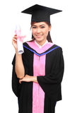 Woman with graduation cap and gown with arm raised holding diplo Stock Photos