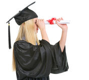 Woman in graduation gown looking through diploma Royalty Free Stock Images