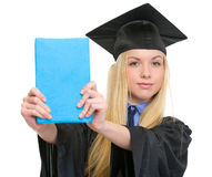 Young woman in graduation gown showing book. Isolated on white Stock Photo