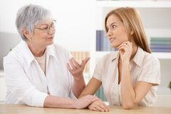 Young woman and grandmother chatting at home. Young women visiting grandmother at home, chatting, smiling royalty free stock images