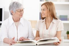 Young woman and grandmother having fun. Young women and grandmother looking at photo album at home, having fun, smiling at each other Stock Photos