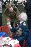 Young woman grants flowers to a war veteran. They both smile. Stock Images
