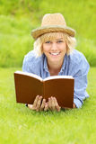 Young woman on a grass with a book Royalty Free Stock Photo
