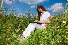 Young woman on the grass field with a laptop. Smile. In white dress. Computer rests on his knees Stock Image