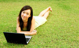 Young Woman on Grass with Laptop Stock Images