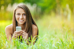 Young woman grass lying with phone Stock Images
