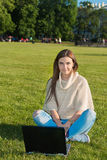 Young woman on a grass in the park or garden using laptop Royalty Free Stock Photo