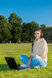 Young woman on a grass in the park or garden using laptop Stock Photo