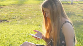 Young woman on grass with phone stock video