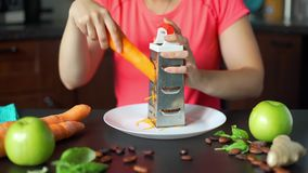 Young woman grating carrot in the kitchen. Making a vegetable smoothie process. Healthy eating, cooking, vegetarian food and dieting concept stock video footage
