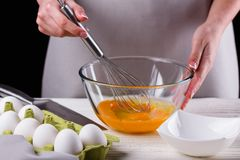 Young woman in a gray aprons breaks the eggs.  stock photography