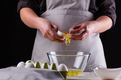 Young woman in a gray aprons breaks the eggs.  stock photos