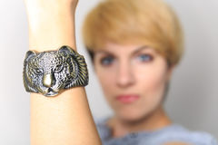 Young woman on a gray background with a bracelet in the form of tiger head. Horizontal photo Stock Images