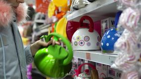 A young woman chooses a green steel kettle in the supermarket. stock video footage