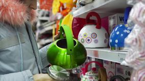 A young woman chooses a green steel kettle in the supermarket. A young woman in a gray coat chooses a green steel whistling kettle in the supermarket in the