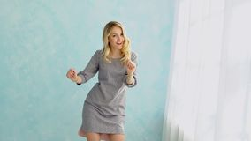 Young woman in a gray dress is dancing against a blue wall background royalty free stock photography
