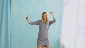 Young woman in a gray dress is dancing against a blue wall background.  stock footage