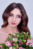 Young woman with gray eyes and long brown hair holding pink flow Royalty Free Stock Images