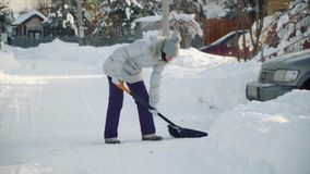 Young woman cleans snow by shovel for car in suburbs in winter. stock footage