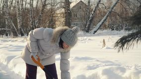 Young woman removes snow by shovel in suburbs in winter. stock footage