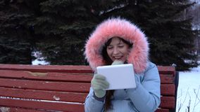 A young woman in a warm jacket uses a digital tablet in the park in the winter. A young woman in a gray warm coat sits on a bench and uses a digital tablet, in stock video footage