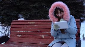 A young woman in a warm jacket uses a digital tablet in the park in the winter. A young woman in a gray warm coat sits on a bench and uses a digital tablet, it` stock video