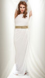 Young woman in greek inspired white dress, smiling Royalty Free Stock Image