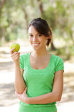 Young woman with green apple. Portrait of young woman with green apple, smiling and looking in camera Royalty Free Stock Photos