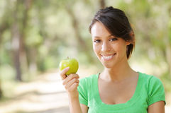 Young woman with green apple. Portrait of young woman with green apple, smiling and looking in camera Stock Photos